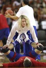 Andrea Hudy, associate director of strength and conditioning for the men's and women's basketball teams, stretches center Jeff Withey before tipoff against Texas on Saturday, Jan. 21 at the Frank Erwin Center in Austin. Hudy's responsibilities reach far beyond stretching and include tailoring workout regimens for individual players and monitoring calorie intake