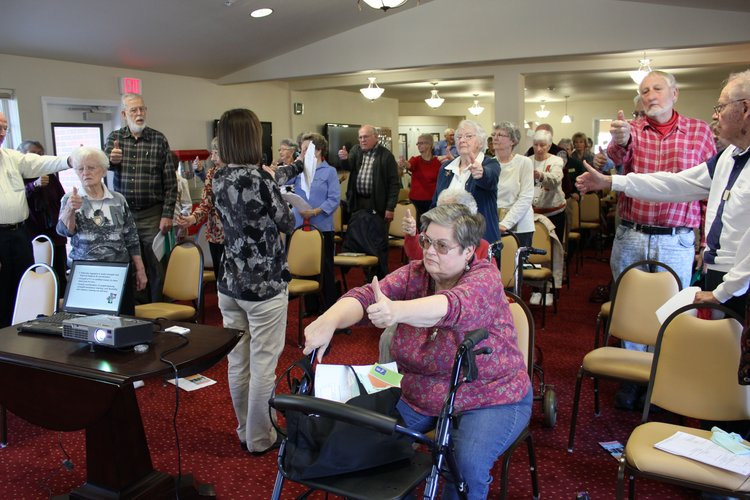 Stacia Bone, a physical therapist at Lawrence Memorial Hospital's Therapy Services, leads a group of older adults in an exercise to help improve their balance and coordination. She was one of the speakers during a program about fall prevention Tuesday, Jan. 31, 2012, at Meadowlark Estates.