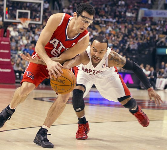 Atlanta Hawks guard Kirk Hinrich, left, and Toronto Raptors guard Jerryd Bayless vie for the ball during the first half of an NBA basketball game in Toronto on Tuesday, Jan. 31, 2012.