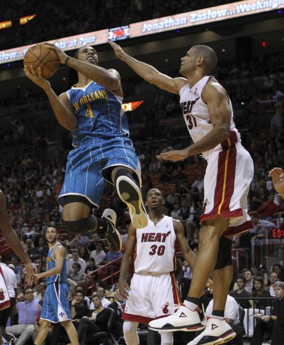 New Orleans Hornets shooting guard Xavier Henry (4) goes to the basket as Miami Heat small forward Shane Battier (31) defends duringan NBA basketball game in Miami, Monday, Jan. 30, 2012.