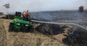 Grass fires were reported throughout Douglas County Thursday. Some were controlled burns, getting grass ready for the spring rains. Lawrence parks department employee Lenny Irey sprays some water on a fire just south of Eagle Bend Golf Course.