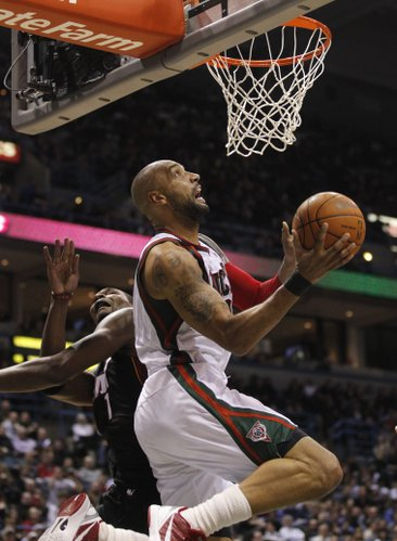 Milwaukee Bucks' Drew Gooden, right, puts up a shot against Miami Heat's Chris Bosh, left, during the second half of an NBA basketball game Wednesday, Feb. 1, 2012, in Milwaukee. The Bucks won 105-97.