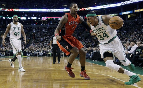 Boston Celtics forward Paul Pierce (34) drives the baseline around Toronto Raptors forward James Johnson (2) as Celtic's Chris Wilcox (44) looks on during the first half of their NBA basketball game in Boston, Wednesday, Feb. 1, 2012.