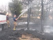 Firefighters from the Fairmount Township Fire Department in Basehor spray down pine trees still smoldering after a grass fire had been stopped Thursday at Wilderson Tree Farm. Crews continued to spray the area for about 30 minutes after stopping the spread of the fire at about 2:30 p.m.