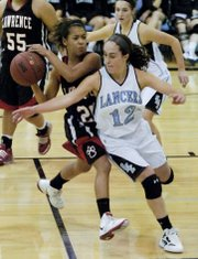 LHS freshman Marissa Pope (25) avoids a steal as Lawrence girls went against Shawnee Mission East Friday, Feb. 3, 2012 in Prairie Village. LHS lost, 51-36.