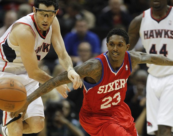Atlanta Hawks guard Kirk Hinrich, left, and Philadelphia 76ers point guard Lou Williams (23) chase down a loose ball in the first quarter of an NBA basketball game on Saturday, Feb. 4, 2012, in Atlanta.