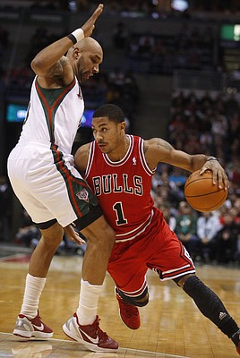 Chicago Bulls' Derrick Rose (1) drives to the basket past Milwaukee Bucks' Drew Gooden, left, during the first half of an NBA basketball game Saturday, Feb. 4, 2012, in Milwaukee.