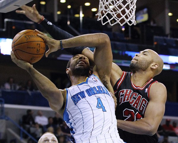 Chicago Bulls forward Taj Gibson (22) fouls New Orleans Hornets guard Xavier Henry (4) in the first half of an NBA basketball game in New Orleans, Wednesday, Feb. 8, 2012.