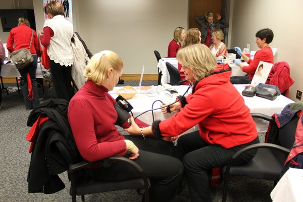Kate Golubski, Lenexa, left, gets her blood pressure checked by Lawrence Memorial Hospital employee Susan Anderson during the 2012 Go Red For Women Luncheon and Expo. About 40 women received blood pressure and cholesterol screenings during the event.