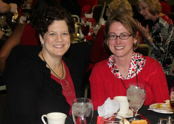 Kathleen Johnson, left, and Monica Taylor, both employees of The World Company, attend the Go Red For Women Luncheon and Expo in the KU Memorial Union ballroom.