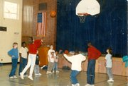 Boys and Girls Club members play basketball in one of the program's school sites. Under the direction of executive director Janet Bremby, the organization began expanding into school sites in the early 2000s.