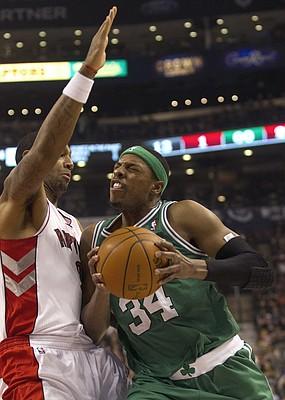 Boston Celtics' Paul Pierce, right, drives to the net past Toronto Raptors' James Johnson during first-half NBA basketball game play in Toronto on Friday, Feb.10, 2012.