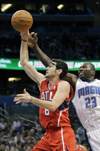 Atlanta Hawks' Kirk Hinrich, left, goes in for a layup past Orlando Magic's Jason Richardson (23) during the first half of an NBA basketball game, Friday, Feb. 10, 2012, in Orlando, Fla.