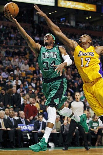 Boston Celtics forward Paul Pierce (34) drives to the basket past Los Angeles Lakers center Andrew Bynum (17) during the first quarter of an NBA basketball game in Boston, Thursday Feb. 9, 2012.