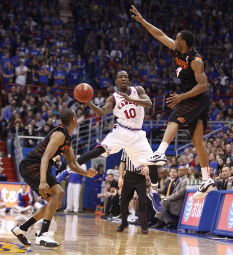 Kansas guard Tyshawn Taylor passes through a trap by Oklahoma State defenders Markel Brown, left, and Brian Williams during the second half on Saturday, Feb. 11, 2012 at Allen Fieldhouse.