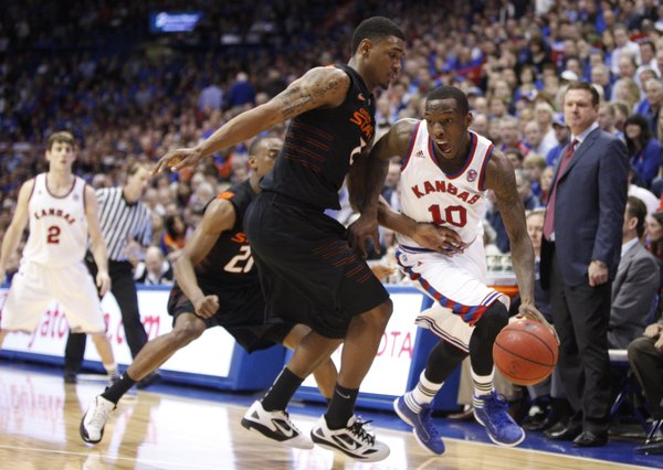 Kansas guard Tyshawn Taylor drives around Oklahoma State forward Le'Bryan Nash during the second half on Saturday, Feb. 11, 2012 at Allen Fieldhouse.
