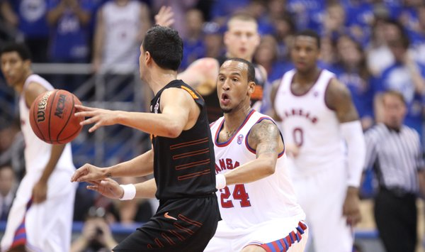 Kansas guard Travis Releford defends against Oklahoma State guard Cezar Guerrero during the first half on Saturday, Feb. 11, 2012 at Allen Fieldhouse.