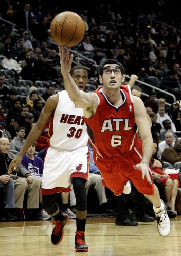 Atlanta Hawks' Kirk Hinrich (6) shoots while fouled by Miami Heat's Norris Cole (30) during the second quarter of an NBA basketball game, Sunday, Feb. 12, 2012, in Atlanta. Miami won 107-87.