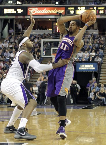 Phoenix Suns forward Markieff Morris, right, looks to pass against Sacramento Kings center DeMarcus Cousins during the fourth quarter of an NBA basketball game in Sacramento, Calif., Saturday, Feb. 11, 2012. The Suns won 98-84.