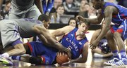 Kansas center Jeff Withey gets on the floor for a loose ball with Kansas State forward Rodney McGruder during the second half on Monday, Feb. 13, 2012 at Bramlage Coliseum. At right is KU guard Elijah Johnson.