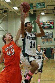 Free State's Cameron Dabney drives for two points against Shawnee Mission Northwest's Jackson Foth (43) on Tuesday, Feb. 14, 2012, at FSHS.