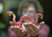 This photograph of my wife holding a dragon for Chinese New Year demonstrates a creative use of a camera's aperture. By selecting a large aperture, represented by an f/stop number of f/2.0 on the camera,  and focusing only on the dragon, I created a very shallow depth of field, throwing the entire background out of focus.