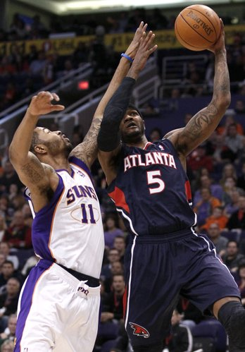 Atanta Hawks' Josh Smith (5) shoots over Phoenix Suns' Markieff Morris (11) during the first half of an NBA basketball game on Wednesday, Feb. 15, 2012, in Phoenix.
