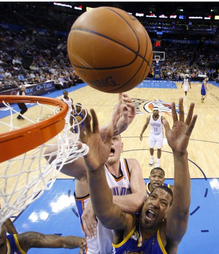 Golden State Warriors forward Dominic McGuire, bottom, rebounds in front of Oklahoma City Thunder centerCole Aldrich, rear, in the fourth quarter of an NBA basketball game in Oklahoma City, Friday, Feb. 17, 2012. Oklahoma City won 110-87.