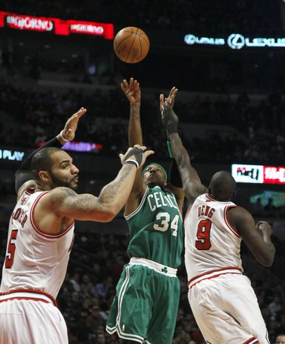 Boston Celtics small forward Paul Pierce (34) shoots over Chicago Bulls power forward Carlos Boozer (5) and small forward Luol Deng (9) during the first half of an NBA basketball game on Thursday, Feb. 16, 2012, in Chicago.
