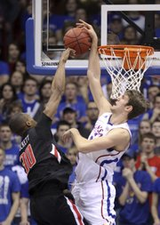 Kansas center Jeff Withey stuffs a shot by Texas Tech forward Jaye Crockett before being called for a foul during the first half on Saturday, Feb. 18, 2012 at Allen Fieldhouse.