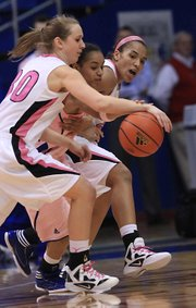 MU defenders Morgan Eye (30) and Bree Fowler squeeze Kansas' Aishah Sutherland for a loose ball on Saturday, Feb. 18, 2012, in Allen Fieldhouse.