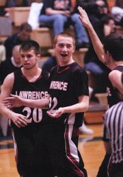 Logan Henrichs, center, celebrates after he hit a three-pointer at the buzzer to end the first half. Lawrence High beat Olathe East, 51-41, on Friday, Feb. 17, 2012, in Olathe.