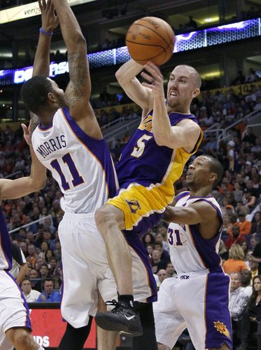 Los Angeles Lakers' Steve Blake looks to pass as Phoenix Suns' Markieff Morris (11) defends during the first half of an NBA basketball game, Sunday, Feb. 19, 2012, in Phoenix.
