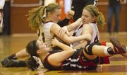 Lawrence High's Anna Wright, bottom, fights with Shawnee Mission North's Shayna Thomas, left, and Cassie Ledgerwood for possession during Lawrence High's game against Shawnee Mission North Tuesday, Feb. 21, 2012, in Overland Park.