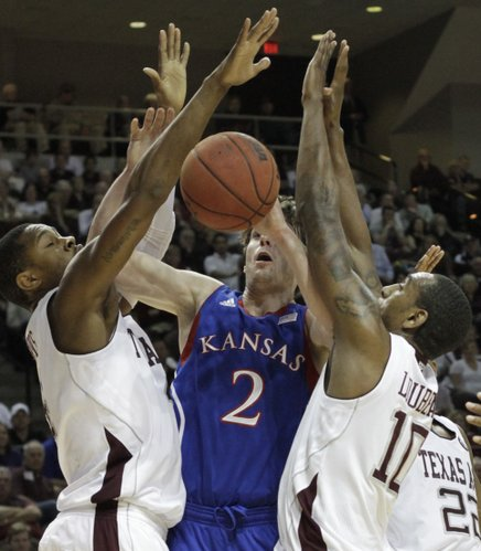 Kansas guard Conner Teahan gets caught between defenders beneath the basket during the first half of the Jayhawks' game against Texas A&M on Wednesday, Feb. 22, 2012, in College Station, Texas.