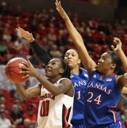Texas Tech's Chynna Brown (00) shoots ahead of Kansas' Aishah Sutherland, left, and Charlicia Harper (24) during their NCAA women's college basketball game in Lubbock, Texas, Tuesday, Feb. 21, 2012.