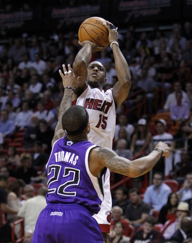 Miami Heat's Mario Chalmers (15) prepares to shoot over Sacramento Kings' Isaiah Thomas (22) in the first half of an NBA basketball game in Miami, Tuesday, Feb., 21, 2012. Miami won 120-108.