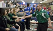 After rolling a strike, Free State bowler Jordan Jump, is congratulated by a line of FSHS girl bowlers during Class 6A regional bowling action at Royal Crest Lanes, Friday, Feb. 24, 2012.