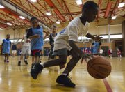 Avion Nelson, 8, dribbles away from defenders during a three-on-three Boys and Girls Club of Lawrence basketball tournament organized by the Kansas University Sports Management Club on Saturday at Robinson Gymnasium on KU's campus.