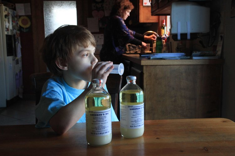 Eight-year-old Matthew Reimer takes a dose of Lorenzo's Oil on Friday, Feb. 24, 2012, as his mother, Emily, prepares a snack in the background. Matthew was diagnosed with a rare, complex genetic disorder called  X-Linked Childhood Adrenoleukodystrophy last year. He takes the oil as part of a study at Kennedy Krieger Institute in Baltimore. The oil has been s