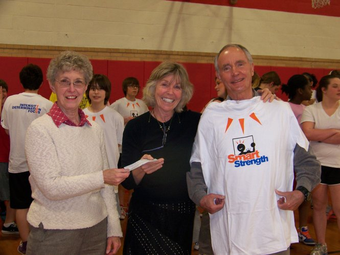 Janet Burnett Huchingson, left, and John Huchingson, treasurer of runLawrence, presented a check to Michel Loomis, center, who is the director of Smart Strength, an after-school athletic program at Liberty Memorial Central Middle School. The donation was made possible through proceeds from the annual Thanksgiving Day 5K organized by runLawrence.