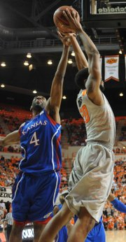 Kansas sophomore Justin Wesley gets his hand on the ball for a block on Oklahoma State's Markel Brown on Monday night.