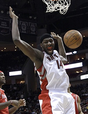 Toronto Raptors' Julian Wright (14) reacts after dunking the ball against the Houston Rockets during the first quarter of an NBA basketball game Friday, Dec. 31, 2010, in Houston.