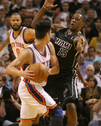 New York Knicks' Jeremy Lin pass the ball against Miami Heat Marios Chalmers during the first quarter of an NBA basketball game at the AmericanAirlines Arena in Miami, Fla., on Thursday, Feb. 23, 2012.