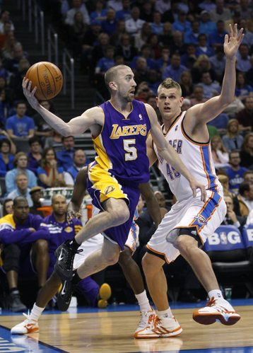 Los Angeles Lakers guard Steve Blake (5) passes off to a teammate in front of Oklahoma City Thunder center Cole Aldrich, right, in the first quarter of an NBA basketball game in Oklahoma City, Thursday, Feb. 23, 2012.