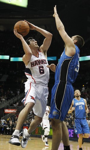 Atlanta guard Kirk Hinrich (6) drives against Orlando power forward Ryan Anderson (33) in the first half of an NBA basketball game on Thursday, Feb. 23, 2012, in Atlanta.