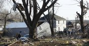 Residents walk the streets the morning after severe storms destroyed several homes and businesses in Harveyville, Kan., Wednesday, Feb. 29, 2012.