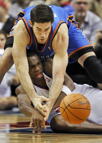 Oklahoma City Thunder forward Nick Collison, top, goes for the loose ball with Philadelphia 76ers guard Jodie Meeks (20) during the second half of an NBA basketball game on Wednesday, Feb. 29, 2012, in Philadelphia. The Thunder won 92-88.