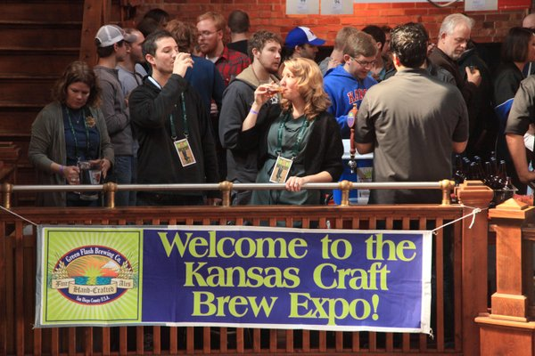 John Bourneuf, left, of Lawrence, and Maria Vopat, of Mission, have a taste of the Kansas Craft Brewers Exposition on Saturday at Abe and Jake's Landing, 8 E. Sixth St., among hundreds of other beer enthusiasts. About 30 regional and national beer vendors were at the event, which sold out within 10 days of going on sale.