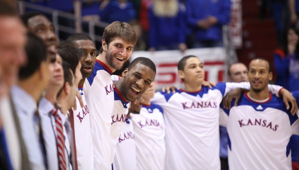 Kansas center Jeff Withey and forward Thomas Robinson laugh with their teammates and coaches as they huddle together for the Alma Mater on Saturday, March 3, 2012 at Allen Fieldhouse.